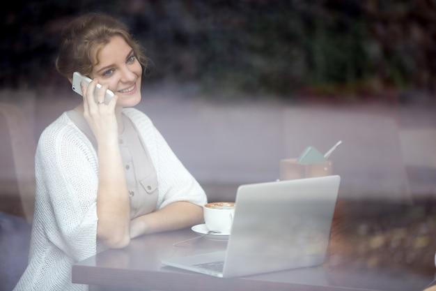 コーヒーショップで電話で話す笑顔実業家 無料写真