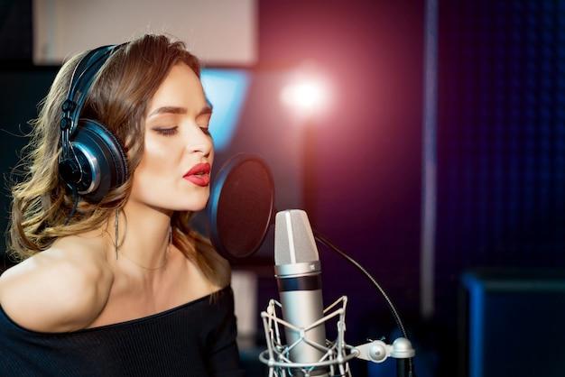 ヘッドフォンと目を閉じてスタジオで歌を録音する女性歌手。 Premium写真
