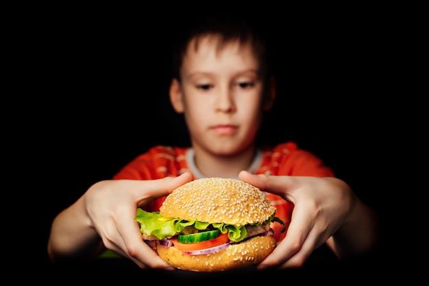 暗いに分離された食欲をそそるハンバーガーを保持している空腹の少年 Premium写真