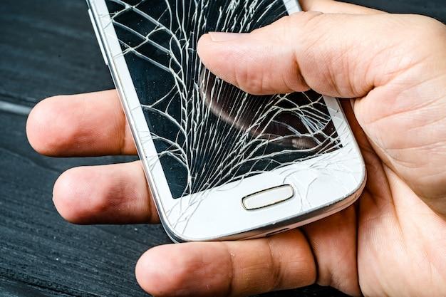 Рука человека держа мобильный телефон с сломленным экраном над темнотой. смартфон с разбитым стеклом сенсорного экрана в руке человека. крупный план Premium Фотографии