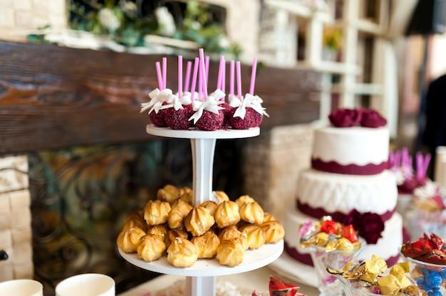 ケーキ、キャンディー、甘いクッキー、ケーキポップスを備えたスタイリッシュなキャンディバー。結婚式の宴会のためのおいしい品揃え。レストラン内のキャンディーバー。 Premium写真