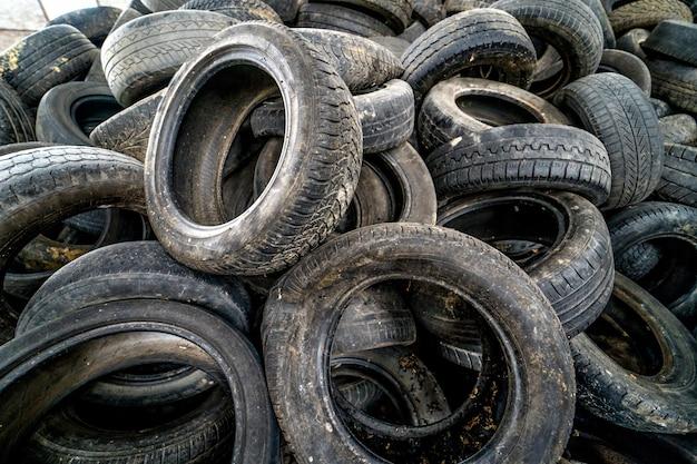 廃棄の準備ができたガベージヒープ。放棄されたゴミ捨て場で古い摩耗タイヤ Premium写真