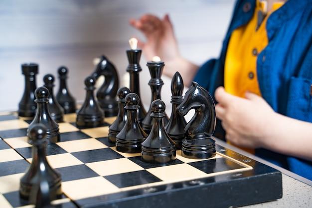 Милый маленький белокурый мальчик делает его движение во время игры в шахматы. развивающая логика настольная игра. Premium Фотографии