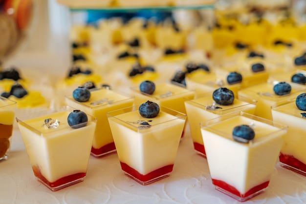 クリームとイチゴの味とブルーベリーの甘いパナコッタがカフェのテーブルにあります Premium写真