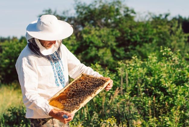 養蜂場で働く若い養蜂家。 Premium写真
