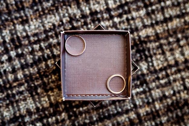 木製の箱に横たわっている結婚指輪のペア。結婚式の装飾。家族、団結、愛の象徴 Premium写真