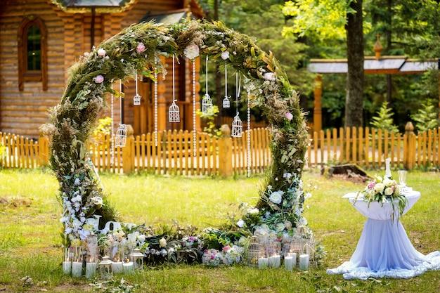 結婚式のアーチ。布の花と緑で装飾されています。松林の中にあります。 Premium写真