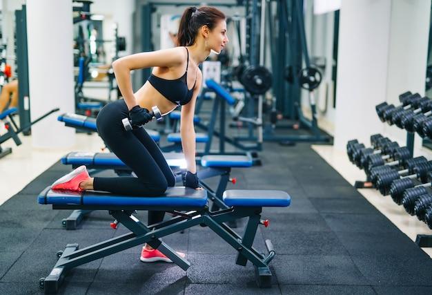 ダンベルで筋肉をポンピング運動の女性。 Premium写真