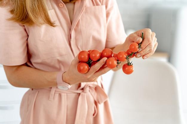 Женщина держит ветку спелых помидоров черри Premium Фотографии