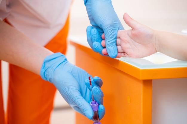 看護師は指から血液検体を収集します Premium写真