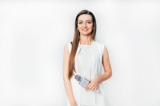 Красивая журналистка в белом костюме стоит с микрофоном в руке Premium Фотографии