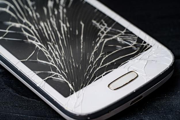 壊れた画面を持つスマートフォン。閉じる。 Premium写真