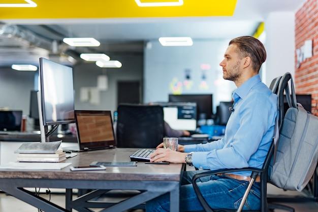 ソフトウェア開発会社のオフィスで多くのモニターを備えたデスクトップコンピューターで作業する男性プログラマー。ウェブサイトの設計プログラミングおよびコーディング技術。 Premium写真