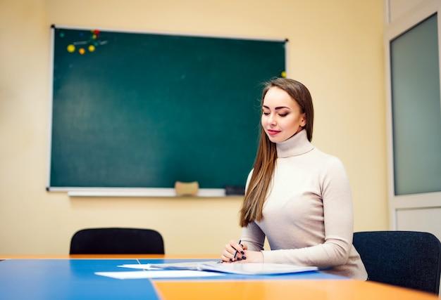 Красивая молодая женщина, сидя за столом с книгами возле доски Premium Фотографии