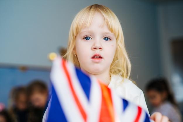 Маленькая девочка играет с британским флагом Premium Фотографии