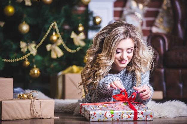 Портрет счастливой молодой рождественской женщины пытается угадать, что находится в подарочной коробке возле елки Premium Фотографии