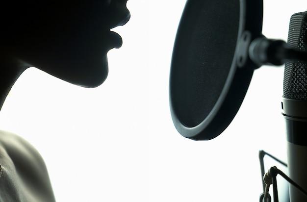 Портрет молодой женщины, запись песни в профессиональной студии. Premium Фотографии