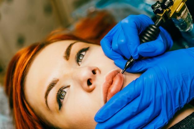 Косметолог, применяя перманентный макияж на губах. молодая женщина проходит процедуру перманентного макияжа губ в салоне тату, крупным планом Premium Фотографии