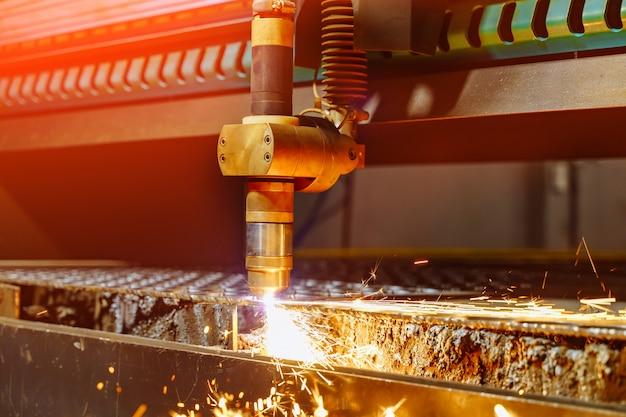 産業用機械による金属板の切断プロセスと火花がレーザーから飛びます。火花を用いた平鋼鋼材加工のレーザー切断技術。 Premium写真