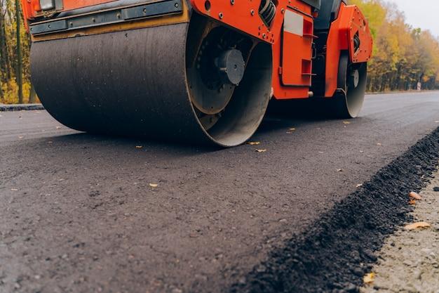 Рабочие работают асфальтоукладчик машины во время строительства дорог. близкий взгляд на дорожном катке работая на новой строительной площадке дороги. Premium Фотографии