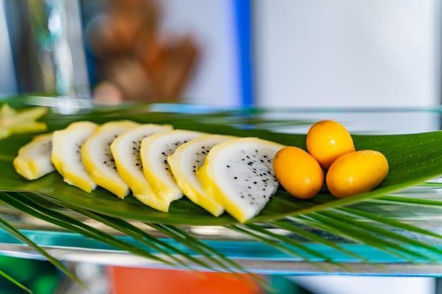 大きな緑の葉の上にゲストのためにきれいに飾られた新鮮なエキゾチックなフルーツ。 Premium写真