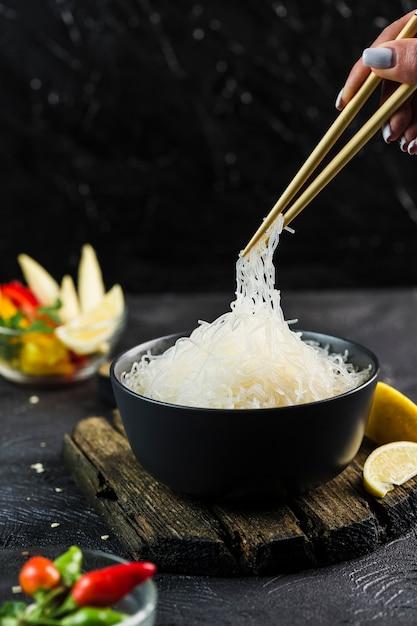 暗い背景、サイドビューのクローズアップに箸で黒ボウルに野菜とセロハンライスヌードル。 Premium写真