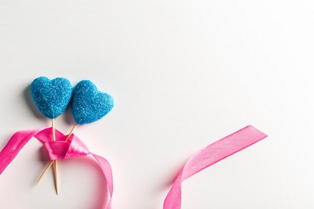 Мармелад в сини сахара в форме сердец на ручках с лентой на белом крупном плане предпосылки с космосом экземпляра. день святого валентина Premium Фотографии