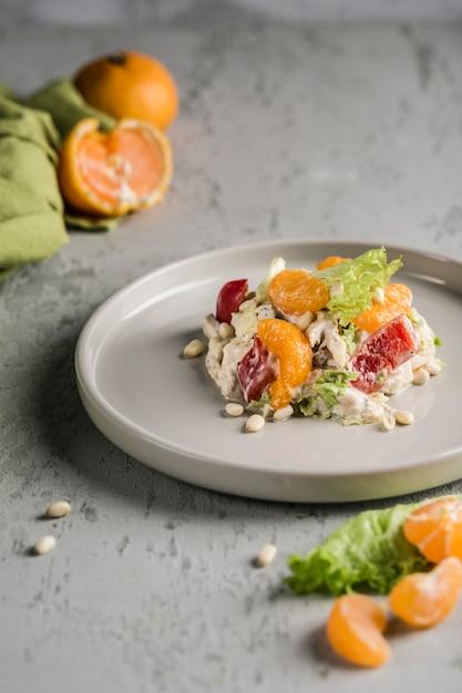 みかん、チキン、松の実、レタス、ピーマンのシーザーソースで味付けしたおいしいサラダ。 Premium写真