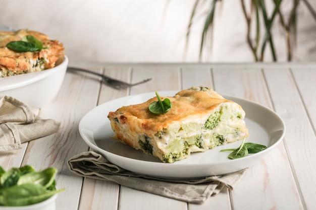 Итальянская лазанья со шпинатом и брокколи на белой тарелке Premium Фотографии