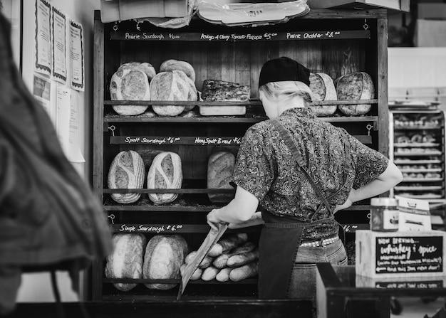Разные виды хлеба на полках пекарни, пекарь женщина Бесплатные Фотографии