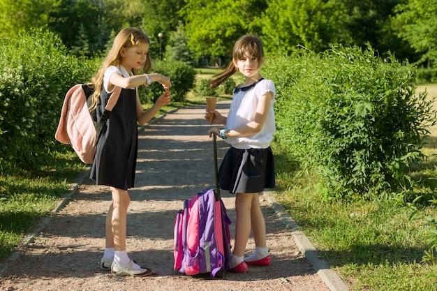 Вид сзади двух школьниц подруг с рюкзаками Premium Фотографии