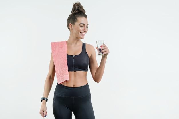 肯定的な笑顔のフィットネス女性飲料水 Premium写真
