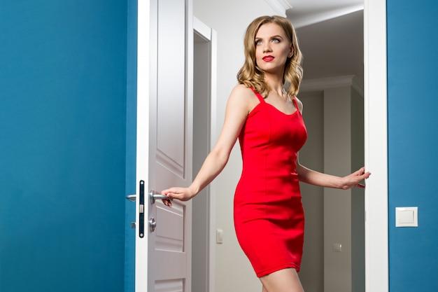 赤いドレスのファッショナブルな女の子がインテリアのドアを開きます Premium写真