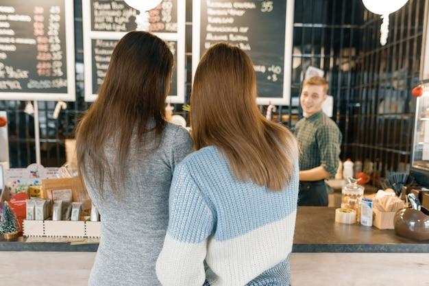 Кофейня, девушки разговаривают с бариста Premium Фотографии