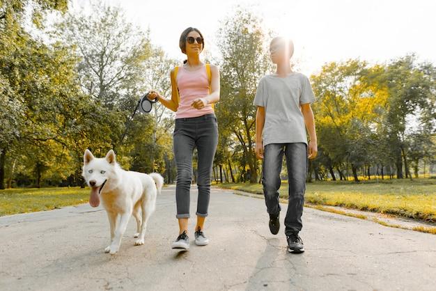 Дети подростки мальчик и девочка гуляют с белой собакой хаски Premium Фотографии