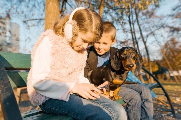 Мальчик и девочка сидят на скамейке в парке с собакой Premium Фотографии