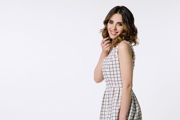 市松模様のドレスで美しいブルネットの少女 Premium写真