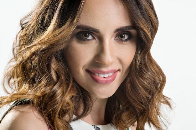 長いウェーブのかかった、光沢のある髪の美しいモデルの女の子 Premium写真