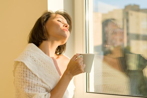 カップと窓の近くに立っている熟女 Premium写真