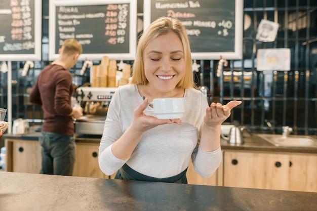 Молодая улыбающаяся бариста с чашкой кофе Premium Фотографии