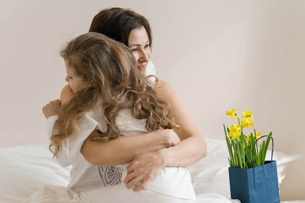 母の日。朝、ママとベッドの中で子供、母親は彼女の小さな娘を抱き締めます。 Premium写真