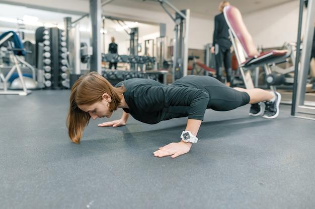 ジムで腕立て伏せの練習を行う若いフィットネス女性 Premium写真