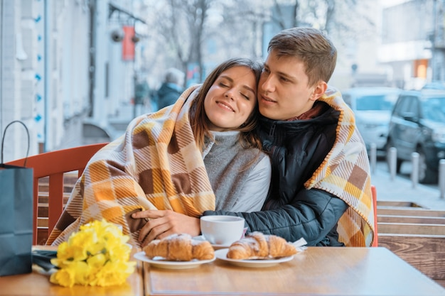 格子縞の下の屋外カフェで愛の若いカップル Premium写真
