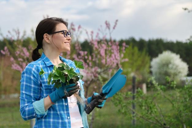ツール、イチゴの茂みの庭で女性の春の肖像画。 Premium写真