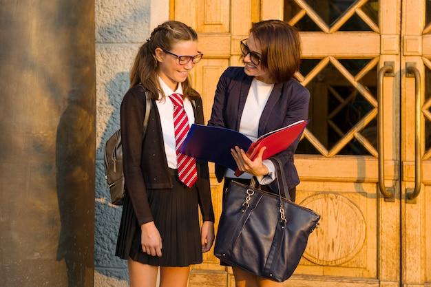 高校の先生が学校の正面玄関近くで女子学生と話しています。 Premium写真