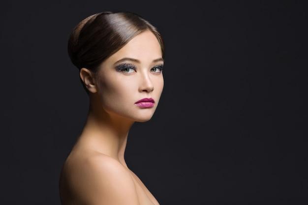 Портрет красоты молодой женщины на темноте Premium Фотографии