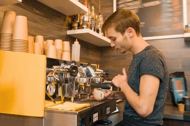 マシンでコーヒーを作る若い男性のコーヒーショップ労働者 Premium写真