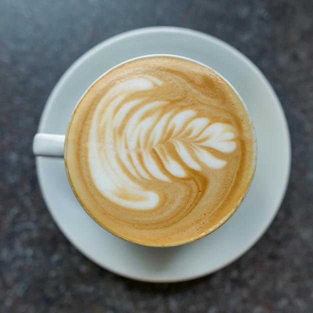 ソーサーと白いカップのコーヒーアート Premium写真