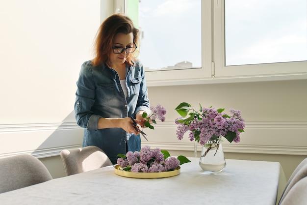 ライラックの枝の花束を作る熟女 Premium写真