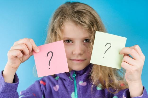 疑問符の付いたステッカーを持って女の子 Premium写真